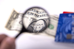 Dollars, bank cards and magnifier Stock Photography