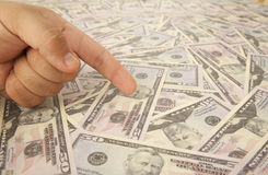 Dollars banknotes background. Forefinger pointing to dollars banknotes Royalty Free Stock Photos