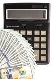 Dollars banknotes and calculator. Hundred dollar bills fan located on the corner of a black calculator isolated on white background Stock Photography