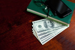 Dollars banknotes, notebook, glasses, phone Royalty Free Stock Image