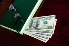 Dollars banknotes, notebook, glasses Royalty Free Stock Photography