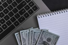 Dollars banknotes whis a sketchpad and black laptop keyboard. Dollars banknotes whis clean sheet of a sketchpad and black laptop keyboard. As a background Royalty Free Stock Photo