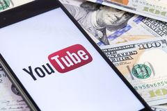 Dollars banknotes and YouTube logo on the screen smartphone. YouTube is a free video sharing application that anyone can watch. Moscow, Russia - March 15, 2019 stock images
