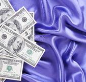 Dollars bills on blue silk fabric Royalty Free Stock Photography