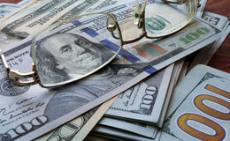 Dollars bills and glasses background. Royalty Free Stock Photos