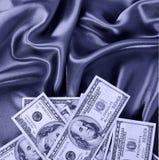 Dollars bills on silk fabric, money Royalty Free Stock Photo