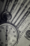 Dollars bills and stopwatch Stock Image