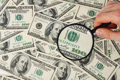 Dollars and black magnifying glass Royalty Free Stock Photo