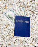 Dollars in blue passport on pebble pebble shingle Royalty Free Stock Photo