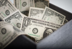 Dollars in a box. Plenty US Dollar bills spilling out of box. An extreme close up Stock Photos