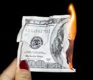 100 dollars brûlant sur un fond noir Photographie stock libre de droits