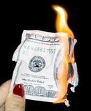100 dollars brûlant sur un fond noir Photo stock