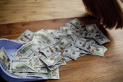 Dollars and broom on wooden floor Royalty Free Stock Photography