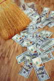 Dollars and broom on wooden floor, closeup Royalty Free Stock Photography
