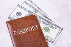 Dollars and brown passport on table. Passport and dollars close-up. Most necessary things for any trip stock photography