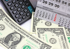 Dollars, calculator  on calendar sheets Stock Photo