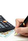 Dollars, calculator and hand with pen on the open notebook. Royalty Free Stock Photo