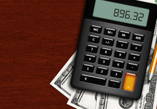 Dollars, calculator and pencil lying on wooden desk Royalty Free Stock Photos