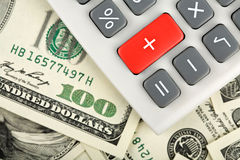 Dollars and calculator with plus red button. Close-up of dollars and calculator with plus red button Stock Photography