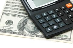 Dollars and calculators isolat. Ed on the white Stock Photography