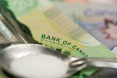 Dollars canadiens, cuillère, et drogues Photographie stock