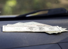 Dollars on a car dashboard under the windshield. American Money Stock Photography