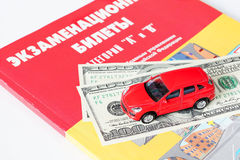 Dollars and the car are to exam Tickets. Hundred-dollar notes and toy car lie on the examination tickets.tuition fees or bribe Stock Photography