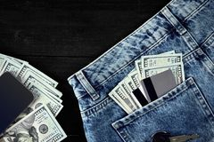 Dollars and cards in your pocket jeans, cash, smart on black wooden background Royalty Free Stock Photo