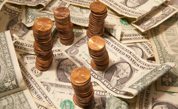 Dollars and Cents. Pennies stacked on dollar bills Stock Image