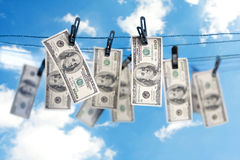Dollars on a clothesline. 100 dollar bills dry on a clothesline Royalty Free Stock Photography