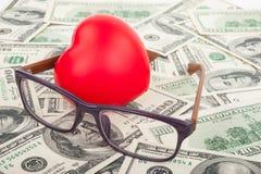 Dollars, coeur rouge et verres Photo stock