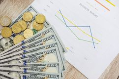 100 dollars and coins on business chart, close-up royalty free stock photo