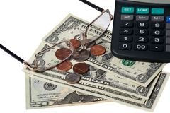 Dollars, coins, glasses and calculator placed on a table Stock Image
