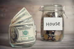 Dollars and coins in jar with house label Stock Images