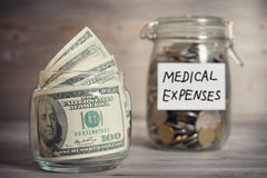 Dollars and coins in jar with medical expenses label Royalty Free Stock Photo
