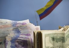 Dollars and Colombian money with Colombian flag waving in the background stock photo