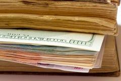 Dollars comme signet dans un vieux livre Images stock