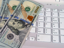 Dollars and computer Stock Photography