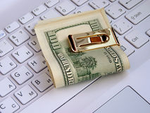 Dollars and computer Stock Photos