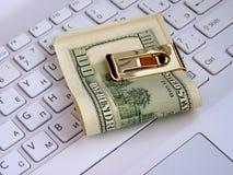 Dollars and computer Stock Photos