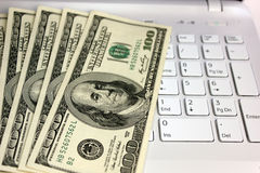 Dollars and computer Royalty Free Stock Photos