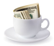 Dollars in a cup. Dollars in white coffee cup Royalty Free Stock Photography