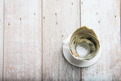 Dollars in cup Stock Image