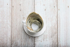Dollars in cup Stock Photos