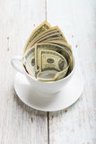 Dollars in cup Stock Images