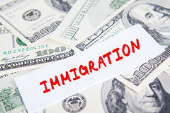 Dollars currency with Immigration word. Pile of dollars currency with Immigration word on the paper, symbolizing Trump Effect in American economy royalty free stock images