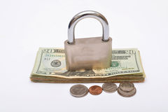 Dollars currency with lock on top and coins Royalty Free Stock Photography