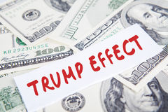 Dollars currency and Trump Effect word. Image of a pile of dollars currency and text of Trump Effect, symbolizing Trump Effect in American economy Royalty Free Stock Photo