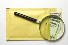 Dollars dans l'enveloppe avec la loupe Photographie stock libre de droits