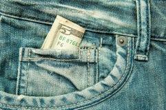 5 dollars dans la poche de jeans Photographie stock libre de droits